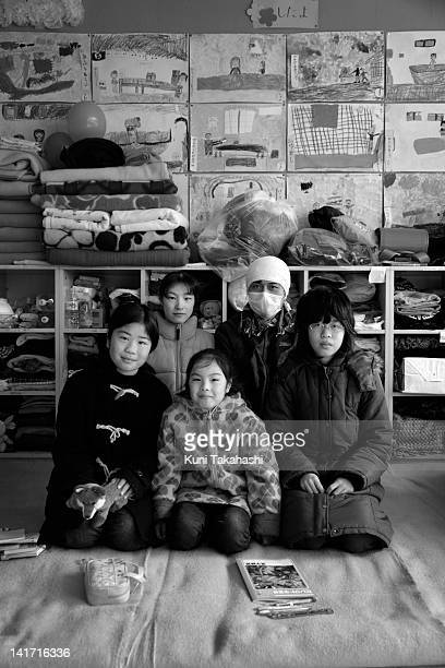 Michiyuki Oikawa poses with his wife Tomomi and daughters Kaede Moe and Sai at an evacuation center March 30 2011 in Minamisanriku Miyagi Japan Their...