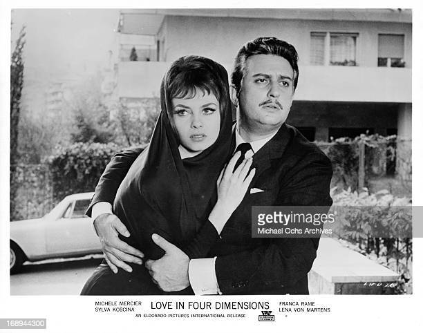 Michèle Mercier holds onto Alberto Bonucci in a scene from the film 'Love In Four Dimensions', 1964.