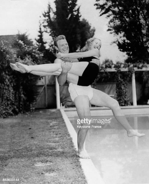 Michèle Morgan dans les bras de son mari l'acteur William Marshall saute dans la piscine de sa propriété à Beverly Hills Californie EtatsUnis en 1946