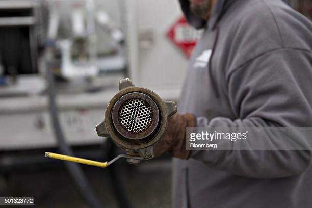 A Michlig Energy worker displays a fuel hose after filling a truck with liquid propane gas from a bulk storage tank in Manlius Illinois US on Monday...