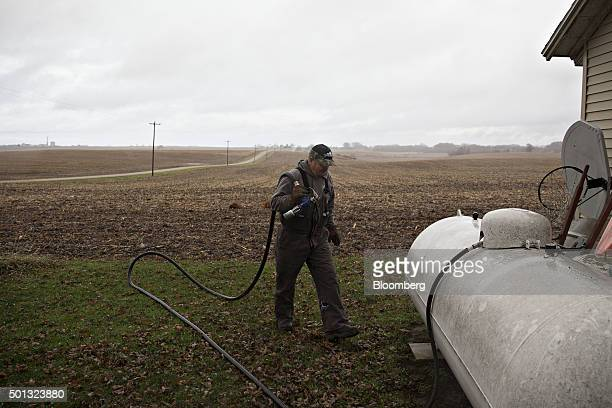 A Michlig Energy worker moves a hose to a liquid propane tank during delivery at a home in Manlius Illinois US on Monday Dec 14 2015 Mild weather...