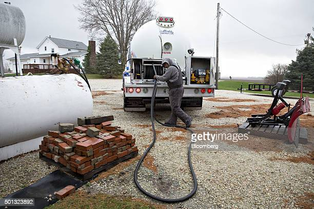 A Michlig Energy worker recoils a hose after delivering liquid propane gas to a home in Manlius Illinois US on Monday Dec 14 2015 Mild weather will...