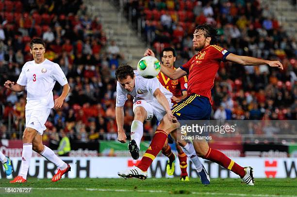 Michu of Spain shoots towards goal under a challenge by Balanovich of Belarus during the FIFA 2014 World Cup Qualifier match between Spain and...