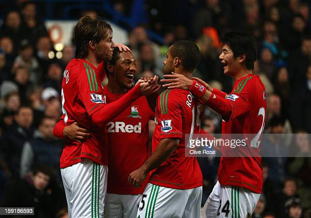 Michu of Swansea City celebrates scoring the opening goal with Jonathan de Guzman and team mates during the Capital One Cup Semi-Final first leg...