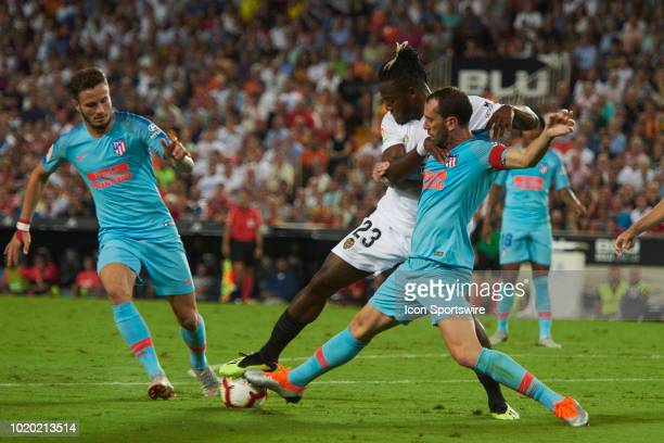 Michy batshuayi forward of Valencia cf competes for the ball with Diego Godin defender and Saul Iñiguez midfielder of Atletico de Madrid during the...
