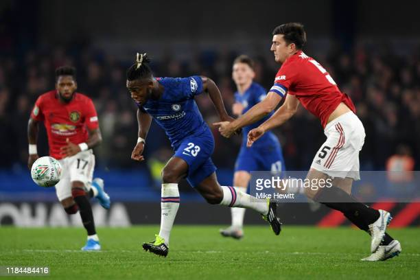 Michy Batshuayi of Chelsea runs with the ball past Harry Maguire of Manchester United before scoring his team's first goal during the Carabao Cup...