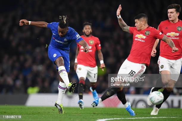 Michy Batshuayi of Chelsea scores his team's first goal as Marcos Rojo of Manchester United attempts to block during the Carabao Cup Round of 16...