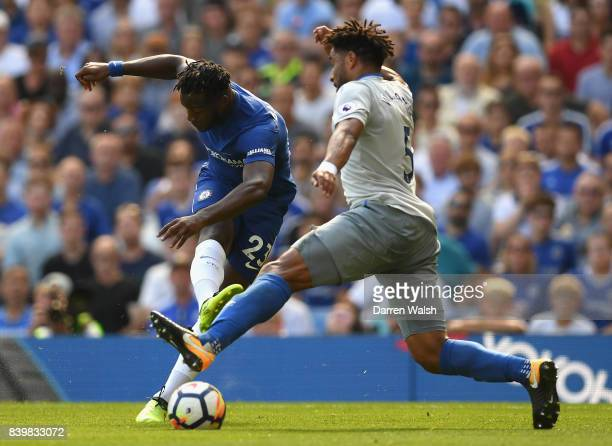Michy Batshuayi of Chelsea shoots as Ashley Williams of Everton attempts to block during the Premier League match between Chelsea and Everton at...