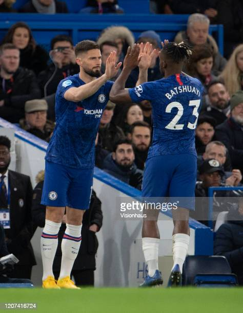 Michy Batshuayi of Chelsea slaps hands with Olivier Giroud as he is substituted during the Premier League match between Chelsea FC and Manchester...