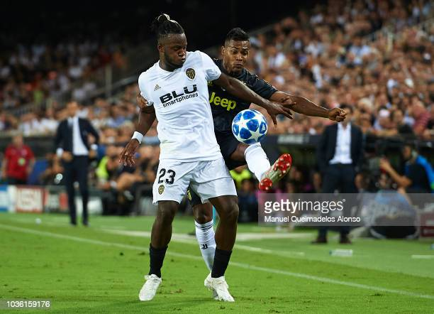 Michy Batshuayi of Valencia competes for the ball with Alex Sandro of Juventus during the Group H match of the UEFA Champions League between Valencia...