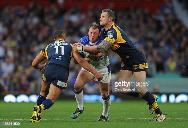 Mick Higham of Warrington Wolves is tackled by Jamie JonesBuchanan and Jamie Peacock of Leeds Rhinos during the Stobart Super League Grand Final...