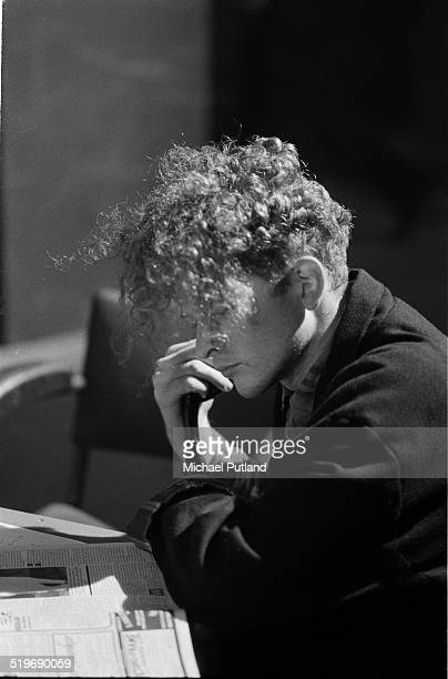 Mick Hucknall of Simply Red taking time out to read a newspaper during downtime at a video shoot in London September 1985