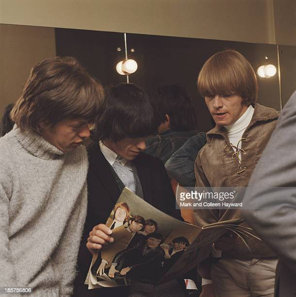 Mick Jagger Bill Wyman and Brian Jones from the Rolling Stones read a magazine featuring a picture of the group on the back cover backstage circa 1964