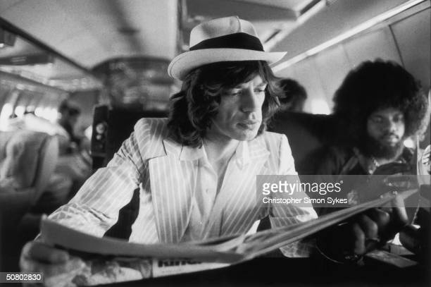 Mick Jagger keeps abreast of current affairs while travelling between concerts in the Rolling Stones' private jet during their 1975 Tour of the...