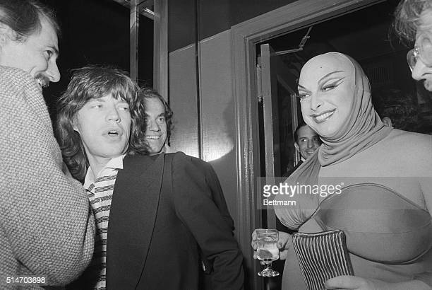 Mick Jagger looks over at Divine an actor performing as a female in the 1976 offBroadway production Women Behind Bars They are attending Andy...