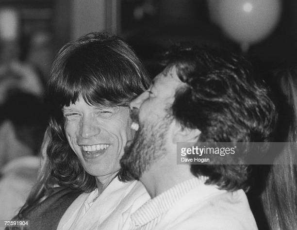Mick Jagger of the Rolling Stones and English guitarist Eric Clapton share a joke at a party given by Bob Geldof at the Hard Rock cafe London to...
