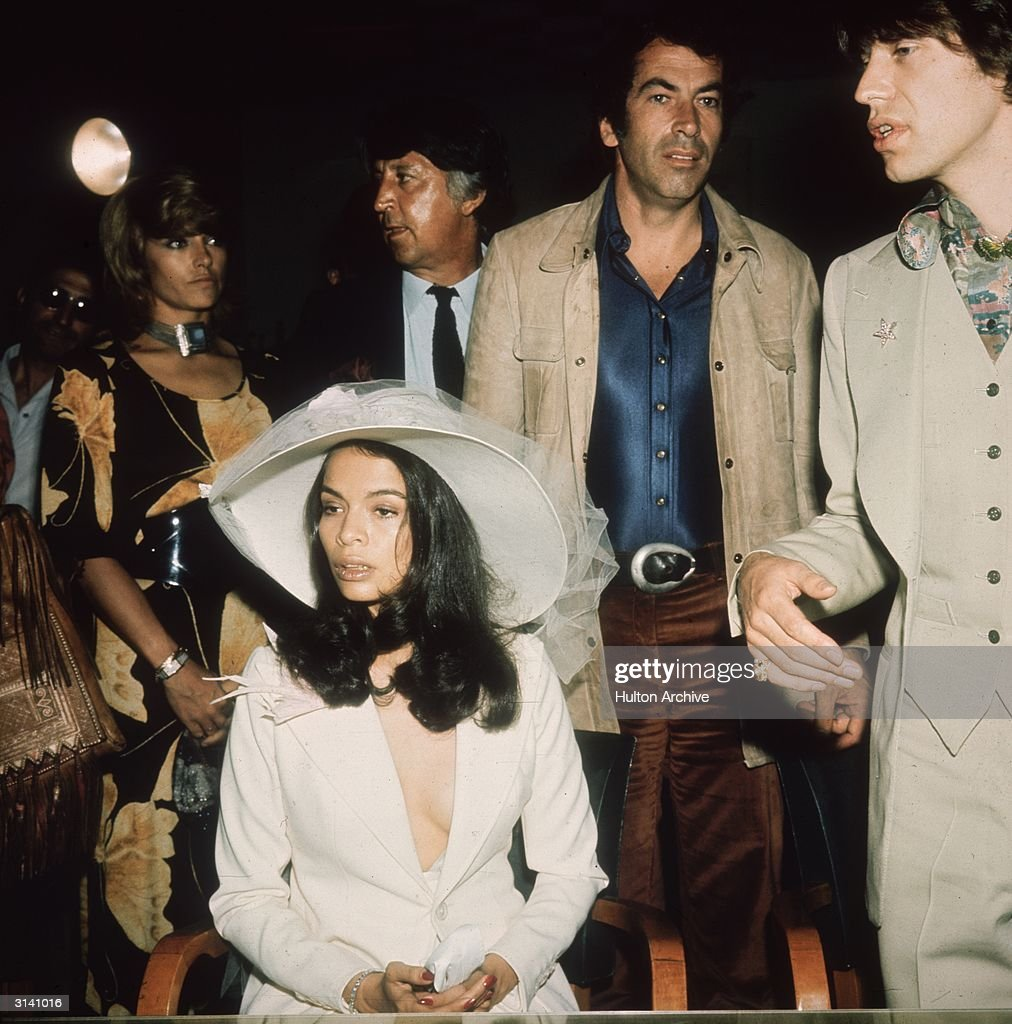 Mick Jagger, the lead singer of the Rolling Stones, with his new wife Bianca on their wedding day. French film director Roger Vadim (1928 - 2000) stands behind the happy couple.