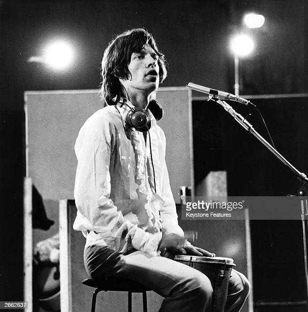 Mick Jagger vocalist with British rock group The Rolling Stones in a recording studio during the filming of 'Sympathy For the Devil' directed by...