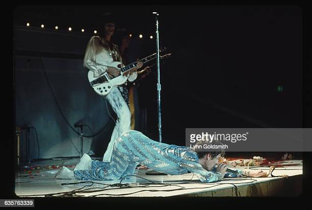 Mick Jagger wearing a sky blue sequined suit crawls on stage during a Rolling Stones concert