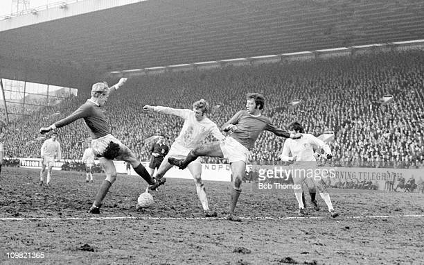Mick Jones of Leeds United is tackled by Manchester United defenders Ian Ure and David Sadler during the FA Cup SemiFinal against Manchester United...