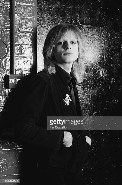 Mick Karn bassiist with British New Wave band Japan poses for a studio portrait beside a painted brick wall in February 1979