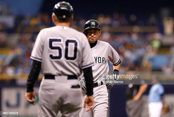 Mick Kelleher of the New York Yankees looks on as Ichiro Suzuki of the New York Yankees comes in to pinch run for Derek Jeter during the 11th inning...