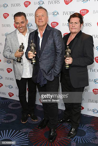 Mick MacNeil Jim Kerr and Charlie Burchill pose for a photo after winning the award for the Outstanding Song Collection in the winners room during...