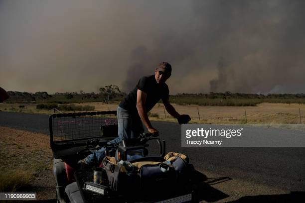 Mick Mason of Mick Mason's Horses keep watch over their property and livestock as firefighter battle to contain spot fires near the Tallaganda...