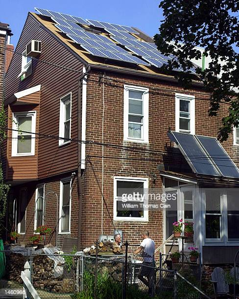 Mick McDermott , of Bensalem, Pennsylvania, speaks with homeowner Andrew Rudin after a solar power tour of his home October 5, 2002 in Melrose Park,...