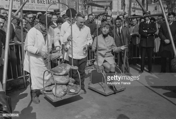 Mick Micheyl marraine 1969 de la foire à la ferraille et au jambon reçoit son poids en jambon lors de cette foire boulevard Richard Lenoir à Paris en...