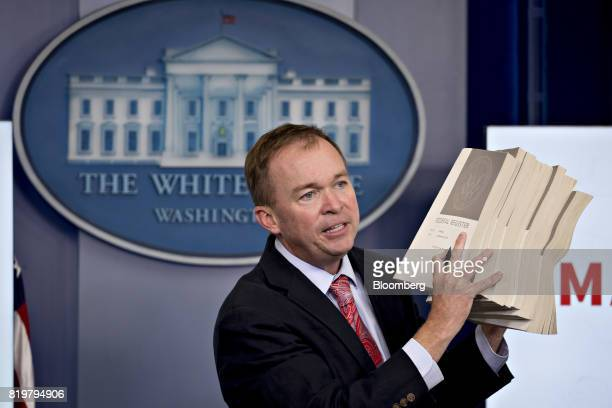 Mick Mulvaney director of the Office of Management and Budget holds up what he described as US President Barack Obama regulations during a White...
