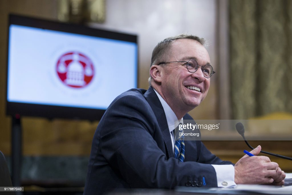 Mick Mulvaney, director of the Office of Management and Budget (OMB), smiles during a Senate Budget Committee hearing in Washington, D.C., U.S., on Tuesday, Feb. 13, 2018. Mulvaney discussed the $4.4 trillion federal budget plan that would slash entitlements and other domestic programs in favor of higher spending on the military and immigration enforcement. Photographer: Zach Gibson/Bloomberg via Getty Images