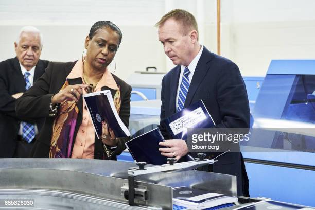 Mick Mulvaney director of the US Office of Management and Budget right holds a volume of the fiscal year 2018 budget while speaking with Davita...