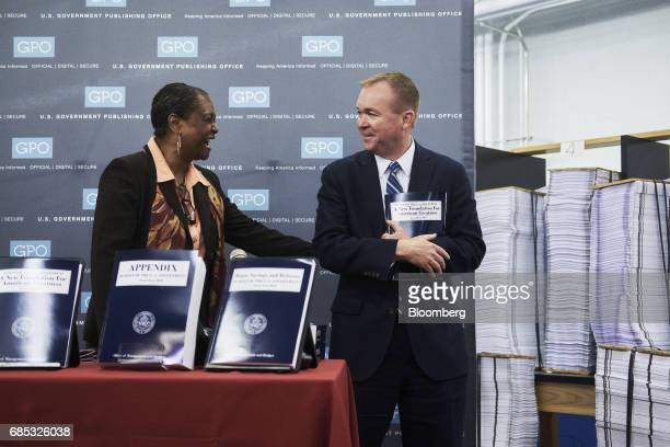 Mick Mulvaney director of the US Office of Management and Budget right holds a copy of the fiscal year 2018 budget appendix while speaking with...