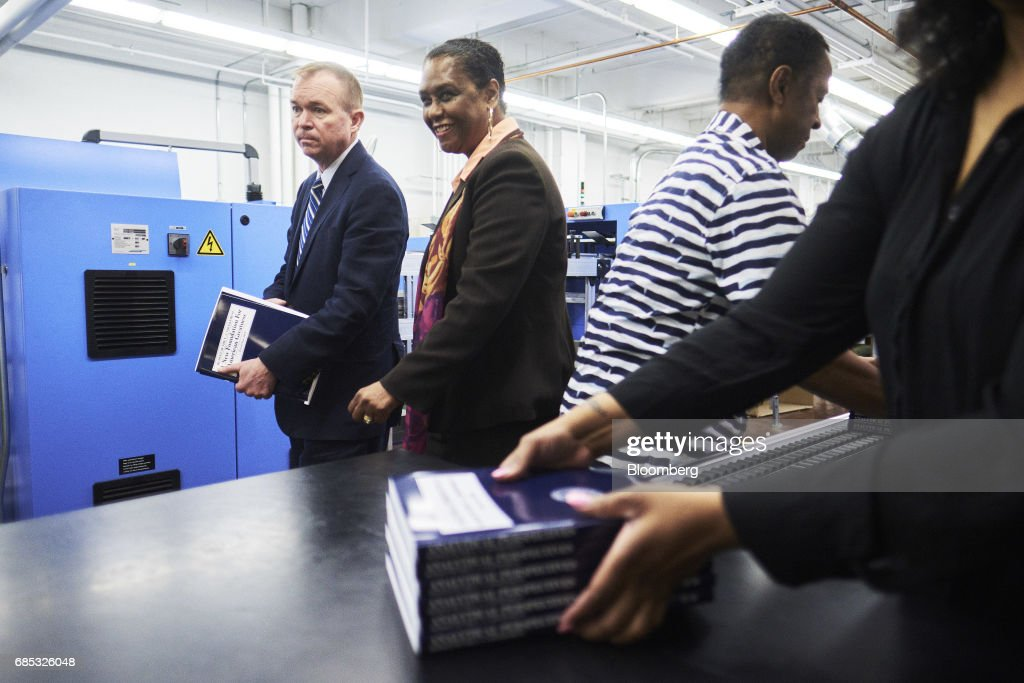 Mick Mulvaney, director of the U.S. Office of Management and Budget, left, holds a copy of the fiscal year 2018 budget appendix while walking with Davita Vance-Cooks, director of the Government Publishing Office (GPO), during a tour of the GPO production facility in Washington, D.C., U.S., on Friday, May 19, 2017. PresidentDonald Trumpwill send to Congress on Tuesday a proposal for balancing the federal budget within 10 years through deep cuts to discretionary and safety net spending, according to a U.S. official. Photographer: T.J. Kirkpatrick/Bloomberg via Getty Images