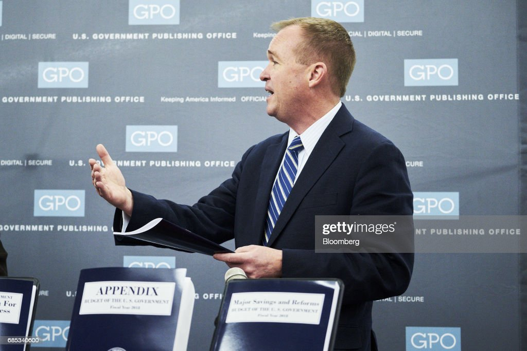 Mick Mulvaney, director of the U.S. Office of Management and Budget, right, speaks while standing over copies of the fiscal year 2018 budget during a tour of the Government Publishing Office (GPO) production facility in Washington, D.C., U.S., on Friday, May 19, 2017. PresidentDonald Trumpwill send to Congress on Tuesday a proposal for balancing the federal budget within 10 years through deep cuts to discretionary and safety net spending, according to a U.S. official. Photographer: T.J. Kirkpatrick/Bloomberg via Getty Images