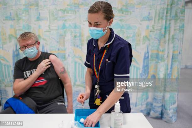 Mick O'Brian from Sunderland receives the AstraZeneca/Oxford University Covid-19 vaccine at the NHS Nightingale North East hospital on January 26,...
