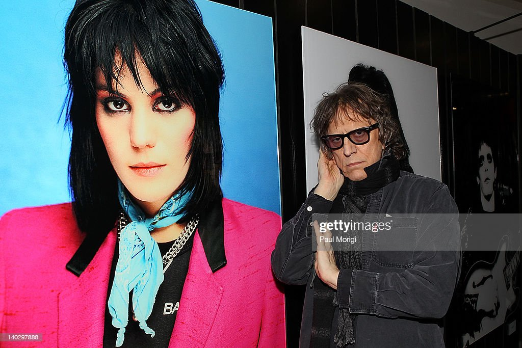 Mick Rock poses alongside his classic photograph of Joan Jett at Mick Rock's Photography exhibit at the W Washington D.C. on March 1, 2012 in Washington, DC.