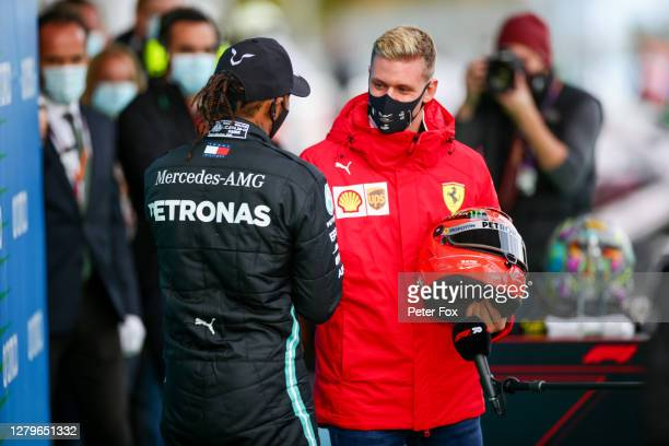 Mick Schumacher of Germany and Ferrari presents Lewis Hamilton of Mercedes and Great Britain with his father Michael Schumacher's helmet to celebrate...