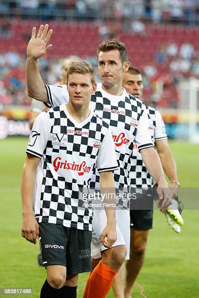 Mick Schumacher son of Michael Schumacher and Miroslav Klose greet supporters after the 'Champions for charity' football match between Nowitzki All...