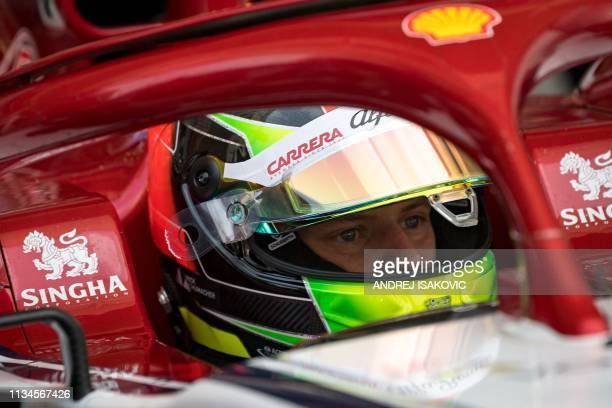 TOPSHOT Mick Schumacher son of seventime world champion Michael Schumacher sits at an Alfa Romeo Racing F1 car at the inseason test at the Sakhir...