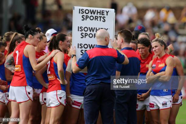 Mick Stinear senior coach of the Demons speaks to the team at the quarter time break during the round three AFLW match between the Fremantle Dockers...