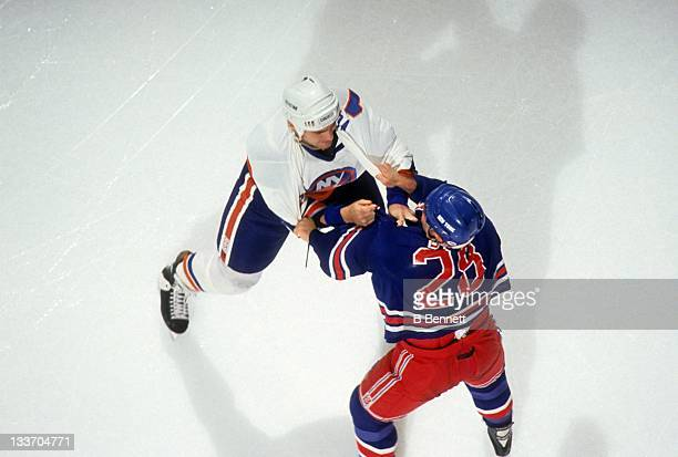 Mick Vukota of the New York Islanders fights with Tie Domi of the New York Rangers during a preseason game in September 1992 at the Nassau Coliseum...