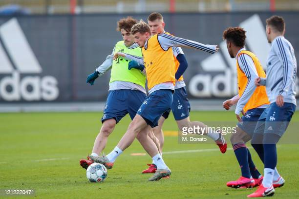 Mickael Cuisance of FC Bayern Muenchen and Javi Martinez of FC Bayern Muenchen fight for the ball during a training session at Saebener Strasse...