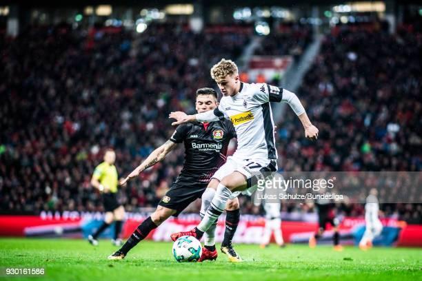 Mickael Cuisance of Moenchengladbach and Charles Aranguiz of Leverkusen in action during the Bundesliga match between Bayer 04 Leverkusen and...