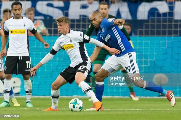 Mickael Cuisance of Moenchengladbach and Naldo of Schalke battle for the ball during the Bundesliga match between FC Schalke 04 and Borussia...