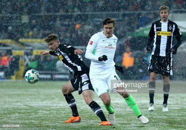 Mickael Cuisance of Moenchengladbach challenges Max Kruse of Bremen during the Bundesliga match between Borussia Moenchengladbach and SV Werder...