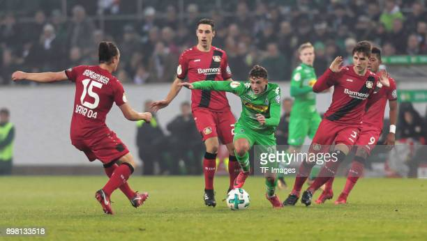 Mickael Cuisance of Moenchengladbach Dominik Kohr of Leverkusen and Panagiotis Retsos of Leverkusen battle for the ball during the DFB Cup match...