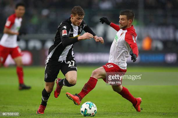 Mickael Cuisance of Moenchengladbach fights for the ball with Daniel Baier of Augsburg during the Bundesliga match between Borussia Moenchengladbach...