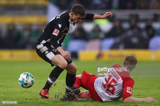 Mickael Cuisance of Moenchengladbach fights for the ball with Martin Hinteregger of Augsburg during the Bundesliga match between Borussia...